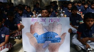 Indian school children hold placards and candles as they participate in prayers for the passengers and crew of Malaysia Airlines flight MH370 at Mirambika School in Ahmedabad, 25 March 2014