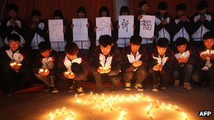 High school students hold candles during a vigil for passengers of the missing Malaysia Airline flight MH370 in Lianyungang, east China's Jiangsu province on 25 March 2014