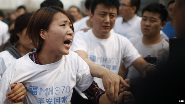 A relative of passengers on missing Malaysia Airlines flight MH370 yells at a security worker while she attends a protest outside the Malaysian embassy in Beijing on 25 March 2014.