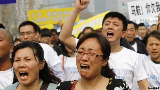 Family members of passengers on board Malaysia Airlines MH370 shout slogans during a protest in front of the Malaysian embassy in Beijing, on 25 March 2014