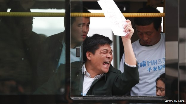 Chinese relatives of passengers on board flight MH370 sit on a bus during a protest on 25 March 2014 in Beijing, China.