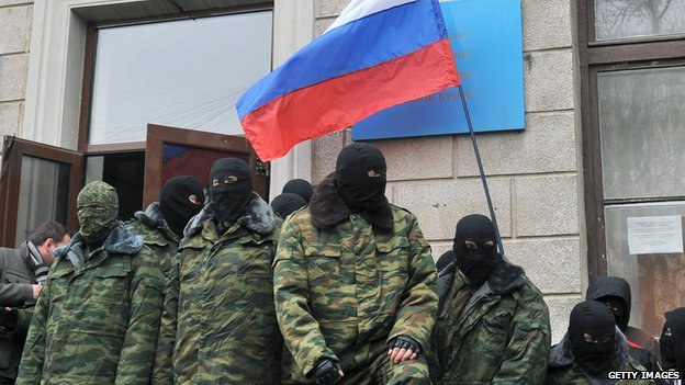 Masked individuals hold a Russian flag at a government building in Crimea on 1 March, 2014.
