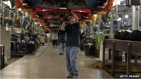 An employee works underneath a Ford Motor Co. Focus vehicle in Wayne, Michigan, on 7 October 2013