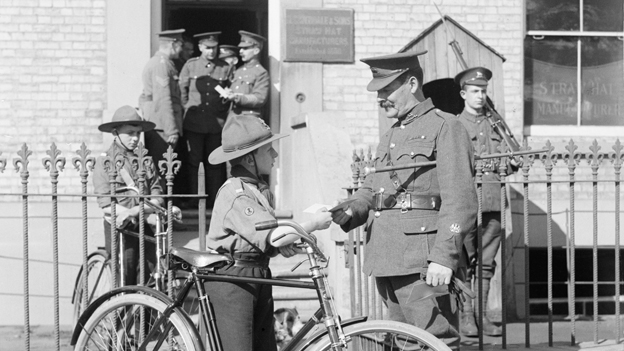 A boy scout with a bicycle collecting a message from a soldier