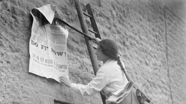 A girl putting a poster on a brick wall