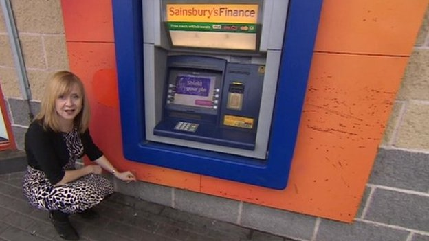 BBC reporter measuring how low the cash machine is off the ground