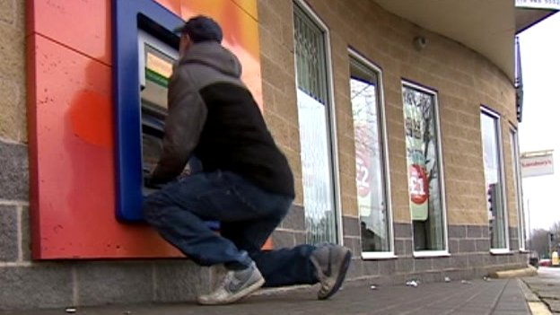 Man kneeling to use a cash machine in Nottingham