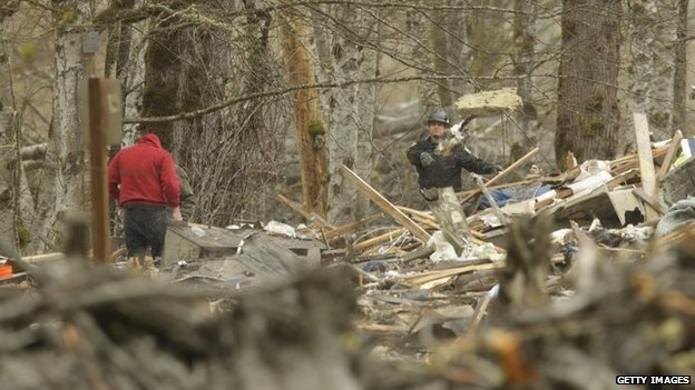 Workers try to clear debris from Saturday's mudslide in Oso, Washington