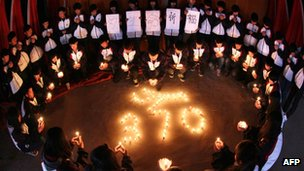 High school students hold candles during a vigil for passengers of the missing Malaysia Airline flight MH370 in Lianyungang, east China's Jiangsu province, 25 March 2014