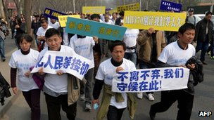 Chinese relatives of passengers on missing Malaysia Airlines flight MH370 march to protest outside the Malaysian embassy in Beijing on 25 March 2014
