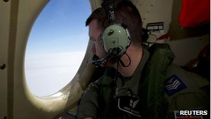 Royal Air Force Sergeant Steve Barnes looks out of an observation window on a Royal Australian Air Force (RAAF) AP-3C Orion, 26 March 2014