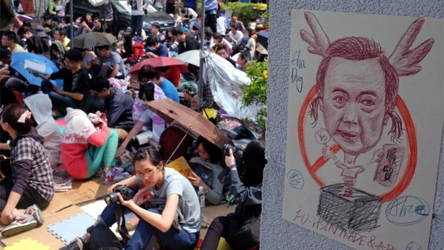 Student protesters sit next to a caricature poster of Taiwan's President Ma Ying-jeou as ongoing protests against a trade agreement with mainland China continue at the parliament in Taipei on 25 March 2014