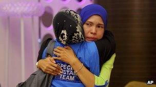 A family member, right, of passengers aboard a missing Malaysia Airlines plane is embraced by a member of Special Assistance Team at a hotel in Putrajaya, Malaysia, Tuesday, 25 March 2014