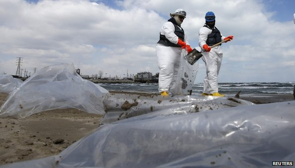 Men in suits cleaning up oil from beach