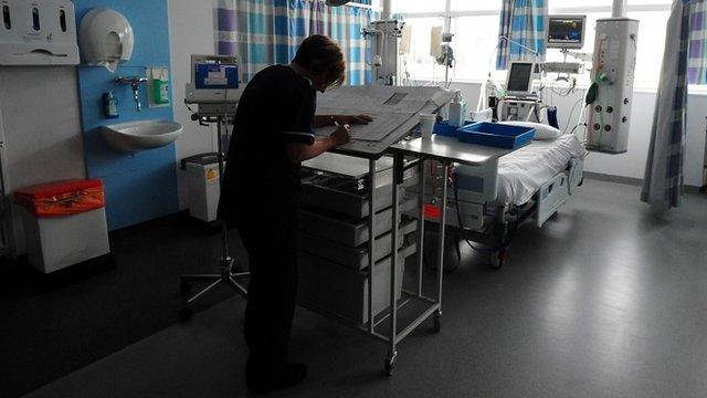 Nurse writes up notes in hospital ward