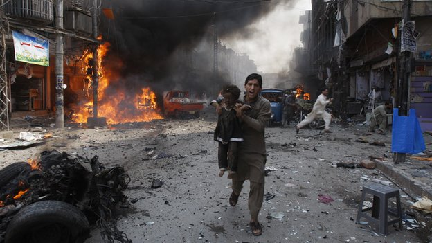 A Pakistani man carrying a child rushes away from the site of a blast shortly after a car exploded in Peshawar, Pakistan, Sunday, Sept. 29, 2013.