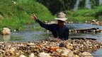 A man removes stones from the river as he pans for gold in Lampang, Thailand