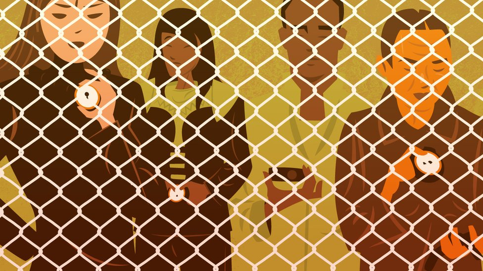 People stand behind a chain-link fence.