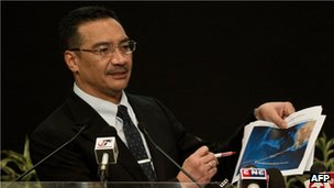 Malaysian Minister of Defence and acting Transport Minister Hishammuddin Hussein shows pictures of possible debris during his statement on the missing Malaysia Airlines flight MH370 at the Putra World Trade Center (PWTC) in Kuala Lumpur on 26 March 2014