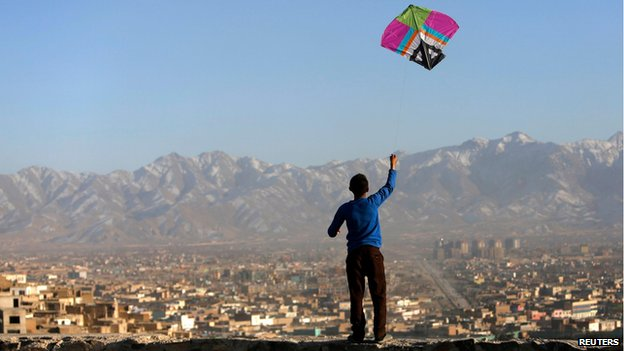 Afghan boy flies a kite on a hillside overlooking Kabul (17 February)