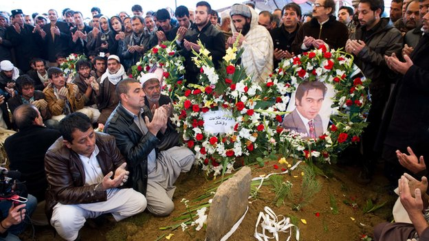 Friends and family pray at Sardar's grave during his funeral in Kabul on 23 March