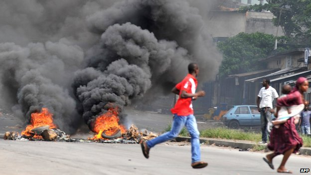 A woman carrying her child runs past supporters of Alassane Dramane Ouattara burning tyres on a street of Abidjan, on 24 February 2011