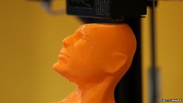 A 3-D printer creates a bust of actor Bruce Willis.