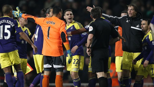 Referee Lee Probert is surrounded by protesting Swansea players after the 2-2 draw at Arsenal
