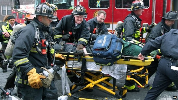 Firefighters take an injured firefighter on a stretcher