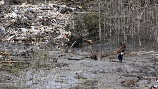 A searcher walks on the mudslide field on 26 March