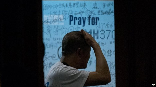 One of the relatives of Chinese passengers on board Malaysia Airlines Flight 370 rubs his head at a hotel in Beijing on 26 March 2014