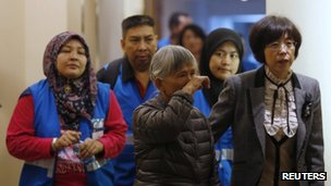 A relative (centre) of a passenger aboard Malaysia Airlines MH370 reacts as she enters a meeting room with volunteers from Malaysia at the Lido Hotel in Beijing, 27 March 2014
