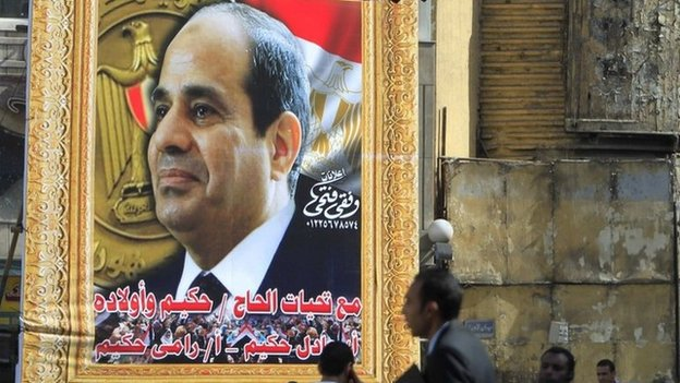 People walk past a large poster of Abdul Fattah al-Sisi in Cairo (26 March 2014)