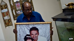 File photo: Subramaniam Gurusamy, 60, shows a portrait of his son Puspanathan who was onboard the missing Malaysia Airlines MH370 flight at his home in Teluk Panglima Garang, outside Kuala Lumpur, 14 March 2014