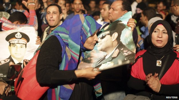 A woman kisses a poster of Egypt's army chief Field Marshal Abdul Fattah al-Sisi