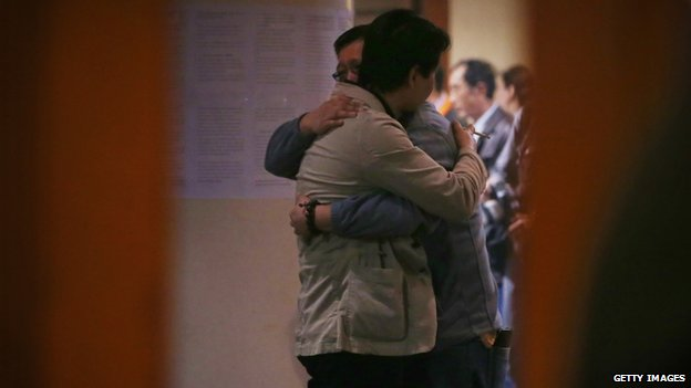 Chinese relatives of the passengers onboard Malaysia Airlines flight MH370 hug each other as they wait for the latest information in Beijing on 20 March 2014