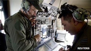 Crew members aboard a Royal Australian Air Force AP-3C Orion aircraft observe navigation maps as they search for missing Malaysian Airlines flight MH370 over the southern Indian Ocean, 27 March 2014
