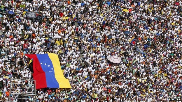 Opposition supporters hold a national flag during a rally against President Nicolas Maduro's government in Caracas (22 March 2014)
