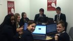 School Reporters sit at their desks in front of computers as they smile for the camera
