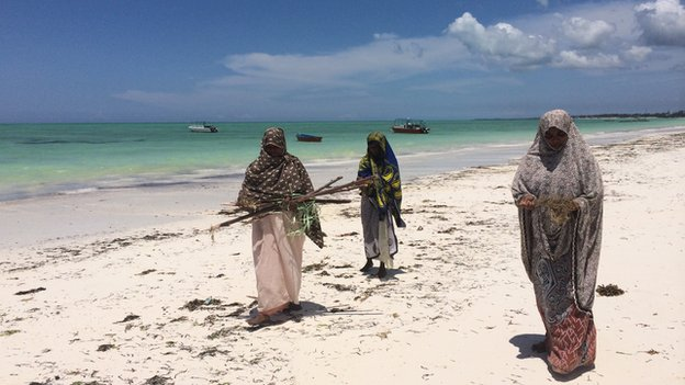 Mwanaisha Makame (R) walks with other women on  the beach in Zanzibar (March 2014)
