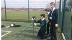 Three boys from Robert May's School prepare the camera for filming on the football pitch