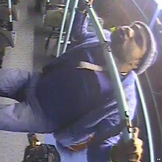 A man does chin-ups from a handrail after assaulting a Polish woman on a bus