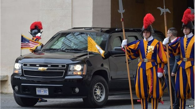 President Obama's car enters the Vatican, flanked by Swiss Guard members