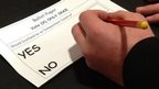 A voter takes part in a mock referendum at a Scottish school