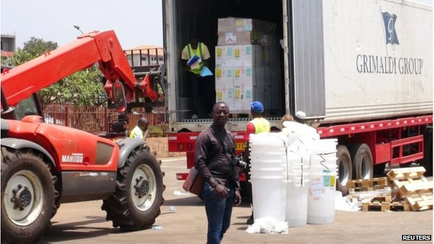 Workers from Doctors Without Borders unload emergency medical supplies from the back of a lorry, to deal with the country's Ebola outbreak