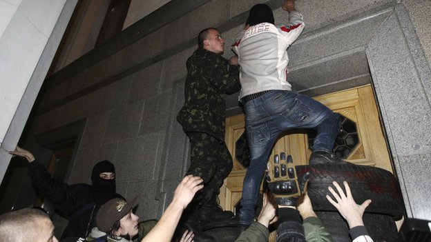 Men climb onto the parliament building as activists of the Right Sector movement and their supporters gather to demand the immediate resignation of Internal Affairs Minister Arsen Avakov, in Kiev March 27, 2014.