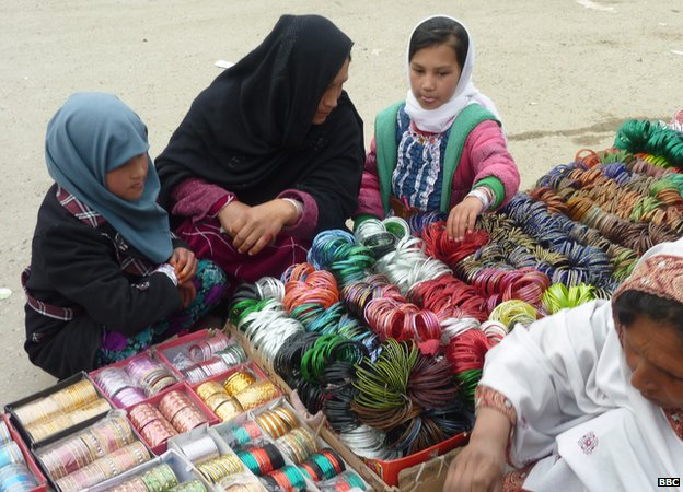 A woman and two young girls browse a stall selling brightly coloured bangles
