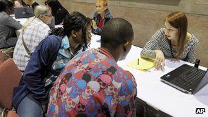 A paid worker guides two Americans through the process of signing up for health insurance (22 March 2014)