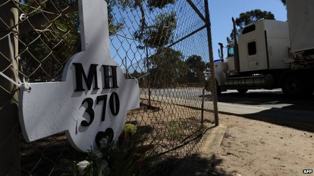 A cross and wreath in memory of those on board the lost Malaysia Airlines Flight MH370 is shown fixed to a fence surrounding Pearce Airbase