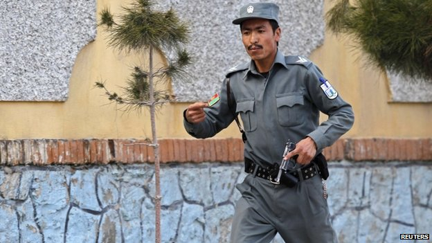 An Afghan policeman runs to the site of an attack in Kabul